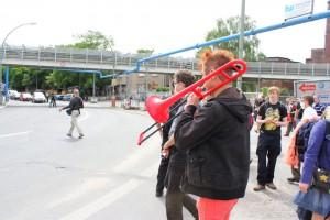 Tobias Trommer gibt mit einer roten Posaune den das Signal zum Flashmob A100 stoppen!
