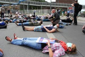 Die Teilnehmer/innen des Flashmobs legen sich auf der geplanten A100-Trasse quer