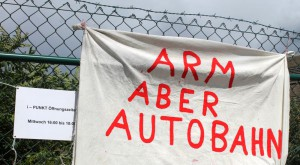 "Transparent ""Arm aber Autobahn"" vor dem A100-Infopunkt in Berlin-Neukölln"
